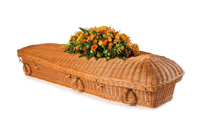 Willow eco coffin with orange flowers on top