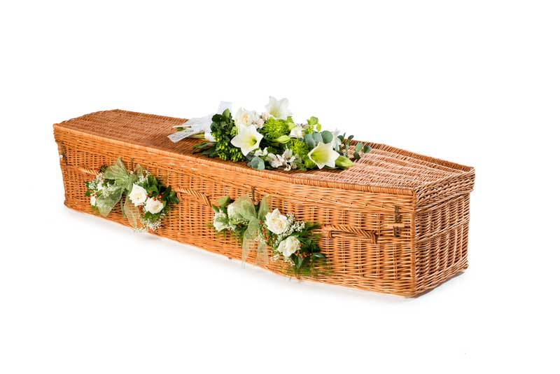 Eco Willow Highsted coffin with white flowers on top