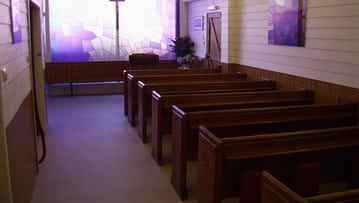 Funeral room with stained glass & pews