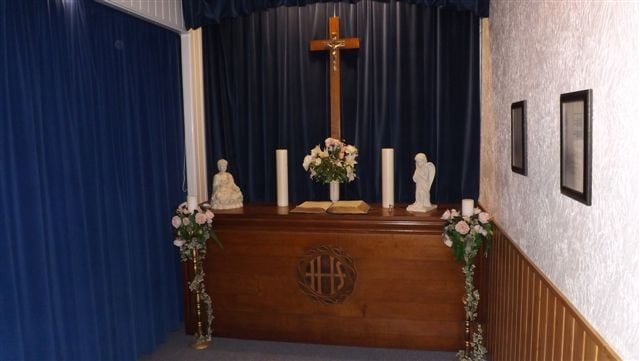 Brown & white funeral room with blue curtains, brown table, candles, book & cross