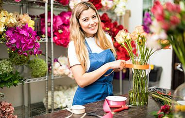 Florist at work tying ribbon around vase