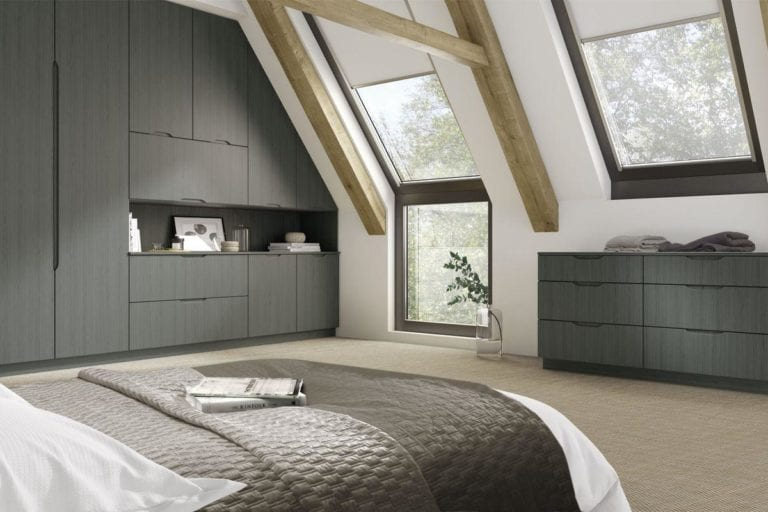 Large, open bedroom with exposed beams, dark grey built in wardrobes & roof windows
