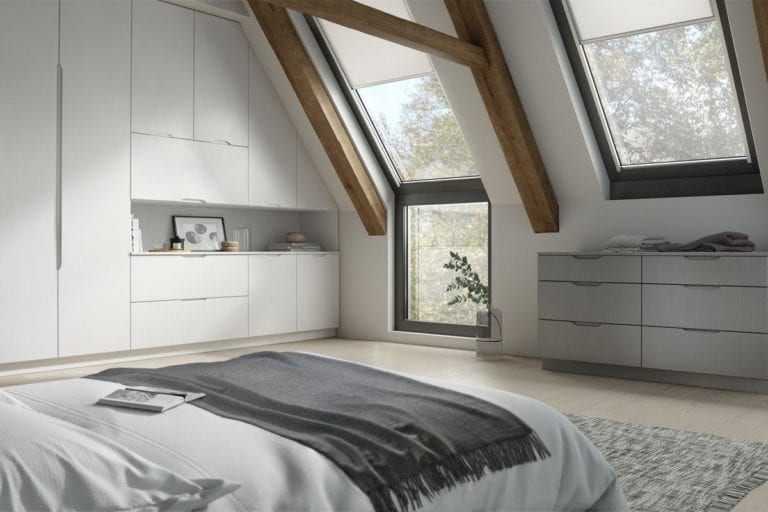 Large, open bedroom with exposed beams, white built in wardrobes & roof windows