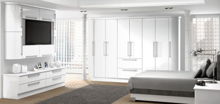 Bright bedroom with shiny white wardrobes & cupboards, a dark grey bed, mounted television & slim white pillars