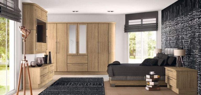 Bedroom with light brown wooden wardrobes, white walls, dark grey bed, long windows & copper standing light