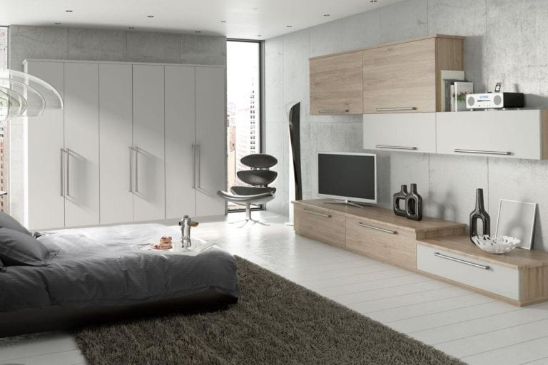 Bright, modern bedroom with white wooden floor, white wardrobes, a grey bed & light brown cupboard units opposite
