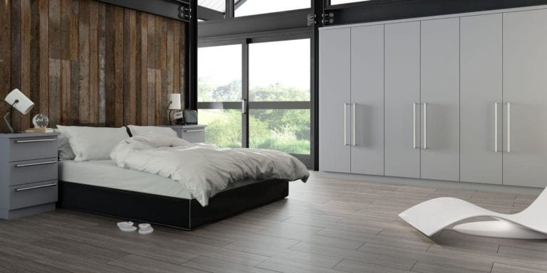Bedroom with grey built in wardrobes, large window, a double bed that backs onto a dark wooden plank wall & flanked by grey bed side cabinets