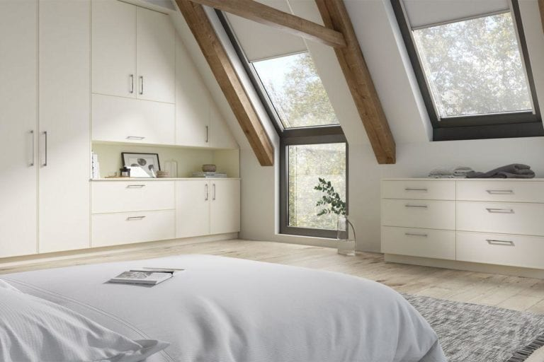 Large, open bedroom with exposed beams, ivory coloured built in wardrobes & roof windows