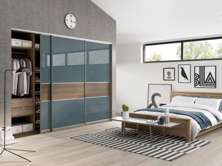 Modern bedroom with grey & white walls, a wooden framed bed & built in sliding wardrobe with blue glass doors