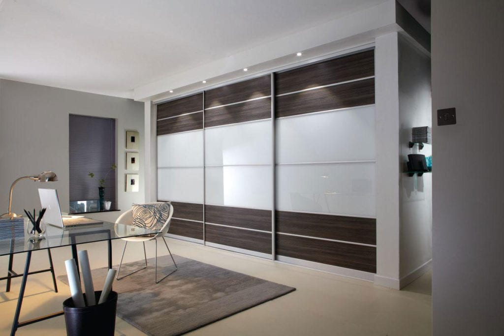 Modern study area with built in wardrobe with dark wooden & glass sliding doors