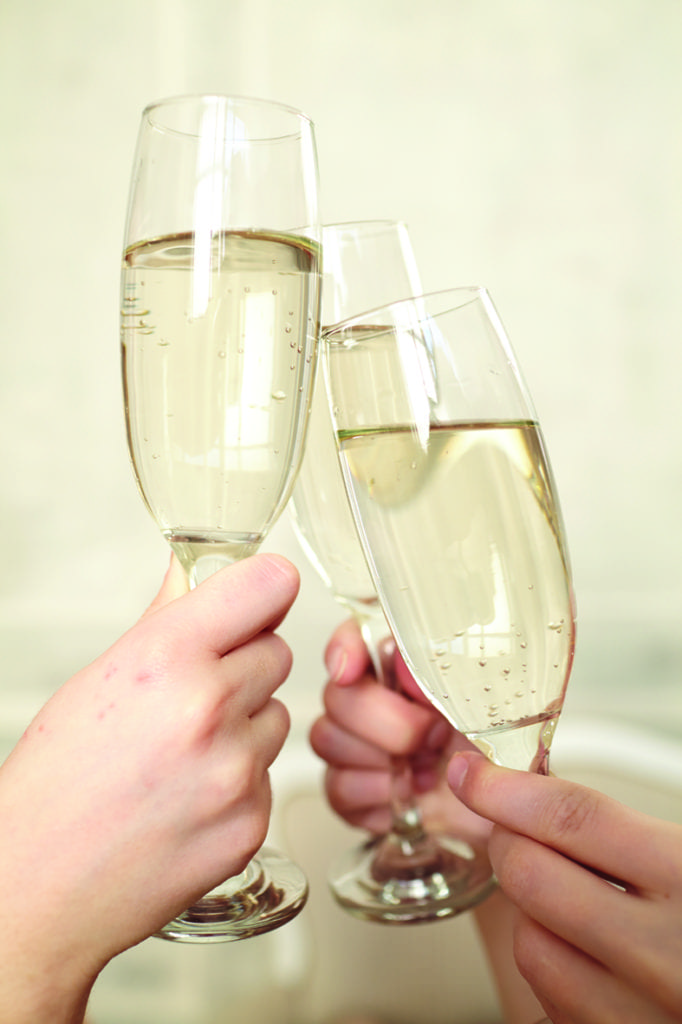 Liquid Indulgence - Glasses of champagne in female hands on a party