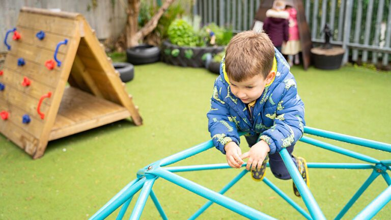 Sunrise Day Nursery - A boy playing on our frame in the playground